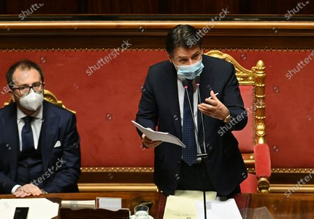 Premier Giuseppe Conte, right, is flanked by Justice Minister Alfonso Bonafede as delivers his speech at the Senate, in Rome, . Conte fights for his political life with an address aimed at shoring up support for his government, which has come under fire from former Premier Matteo Renzi's tiny but key Italia Viva (Italy Alive) party over plans to relaunch the pandemic-ravaged economy