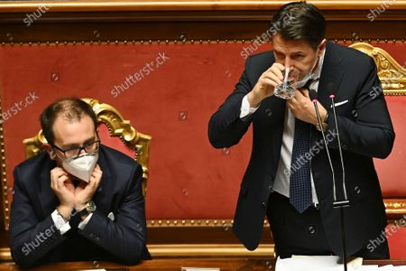 Premier Giuseppe Conte, right, is flanked by Justice Minister Alfonso Bonafede, drinks as he delivers his speech at the Senate, in Rome, . Conte fights for his political life with an address aimed at shoring up support for his government, which has come under fire from former Premier Matteo Renzi's tiny but key Italia Viva (Italy Alive) party over plans to relaunch the pandemic-ravaged economy
