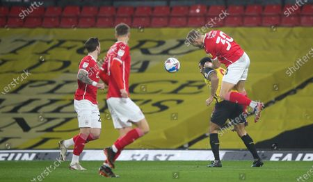 Michal Helik of Barnsley gets up above Troy Deeney of Watford to head