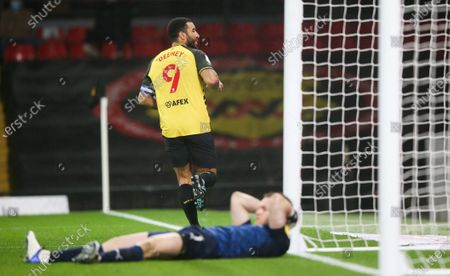 Troy Deeney of Watford scores a goal from the penalty spot and celebrates Jack Walton goalkeeper of Barnsley lies prone