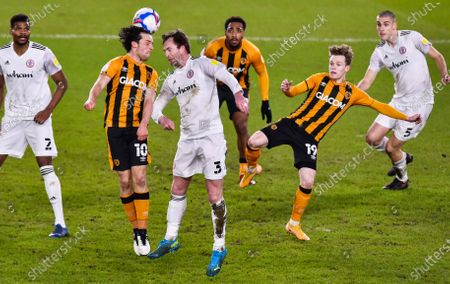 George Honeyman of Hull City wins a header with Mark Hughes of Accrington Stanley as Keane Lewis-Potter lurks