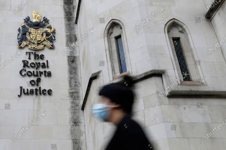 Stock Photo of Pedestrian wears a mask as she passes by the Royal Courts Of Justice, in London, . Meghan, The Duchess of Sussex will ask a High Court judge to rule in her favour in her privacy action against the Mail on Sunday over the publication of a handwritten letter to her estranged father. The case will be heard remotely due to the pandemic