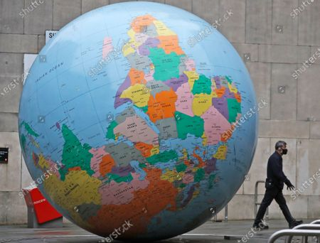 Man wearing a face mask walks past a globe in front of the London School of Economics in London, . The globe designed by Mark Wallinger is called 'The World turned Upside Down'. The U.K. is under an indefinite national lockdown to curb the spread of the new variant, with nonessential shops, gyms and hairdressers closed, most people working from home and schools largely offering remote learning