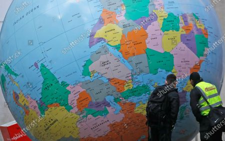 Two men look at a globe in front of the London School of Economics in London, . The globe designed by Mark Wallinger is called 'The World turned Upside Down'. The U.K. is under an indefinite national lockdown to curb the spread of the new variant, with nonessential shops, gyms and hairdressers closed, most people working from home and schools largely offering remote learning