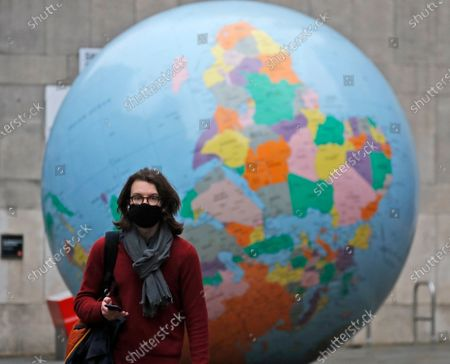 Pedestrian wearing a face mask walks past a globe, in front of the London School of Economics in London, . The globe designed by Mark Wallinger is called 'The World turned Upside Down'. The U.K. is under an indefinite national lockdown to curb the spread of the new variant, with nonessential shops, gyms and hairdressers closed, most people working from home and schools largely offering remote learning