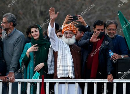 Maulana Fazal-ur-Rehman, center, Maryam Nawaz Sharif, second left, leaders of the Pakistan Democratic Movement, an alliance of opposition parties, wave to their supporters during a rally outside the head office of the Election Commission of Pakistan, in Islamabad, Pakistan