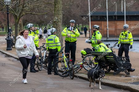 Stock Image of Police on bikes take a rest next to a bench in Hyde Park. Police keep up patrols in Hyde Park in London as Home Secretary Priti Patel warned that there will be tougher enforcement of Covid-19 rules. Today Health Secretary Matt Hancock announced that he will self-isolates after an alert on his Covid-19 app while cases continue to spread through the UK. Last week, Foreign Secretary Dominic Rabb said that lockdown could be lifted in March but with tier systems in place as total Covid-19 deaths reach over 88,000 this weekend.