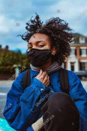 Stock Image of A protestors sits along the concrete wall of the Marcus David Peters Circle, a space reclaimed during the summer for Black Lives Matter protestors.