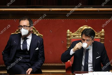 Giuseppe Conte, Italy's prime minister (R) drinks a coffee speaks flanked by Alfonso Bonafede, Italy's justice minister, during a debate in the Senate in Rome, Italy, 19 January 2021. Following the resignation of two ministers in Italian Prime Minister Conte's coalition government over a dispute on spending of EU funds during the pandemic, the Italian government is on the verge of another crisis.