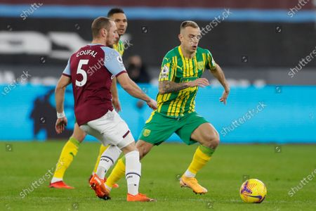 West Bromwich Albion's Kamil Grosicki, right, steers the ball away from West Ham's Vladimir Coufal during an English Premier League soccer match between West Ham and West Bromwich Albion at the London Stadium in London, England, Tuesday Jan.19, 2021