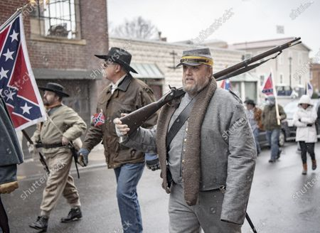 Commemorating Confederate generals Robert E. Lee and Stonewall Jackson. People walking down Main Street and gathering at the Stonewall Jackson memorial. Many participants are dressed in Confederate uniforms from the civil war. Buck Smith carries a musket over his shoulder and wears a uniform. He says he wants to stand up for the ideals of his ancestors