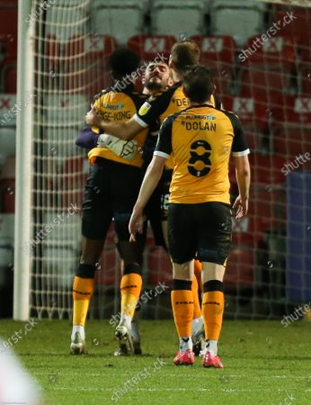 Newport County players celebrate with Newport County goalkeeper Tom King after he scores a long range goal from his own penalty area