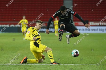 Leon Bailey (R) of Bayer 04 Leverkusen is tackled by Thomas Meunier of Borussia Dortmund during the Bundesliga soccer match between Bayer 04 Leverkusen and Borussia Dortmund at BayArena in Leverkusen, Germany, 19 January 2021.