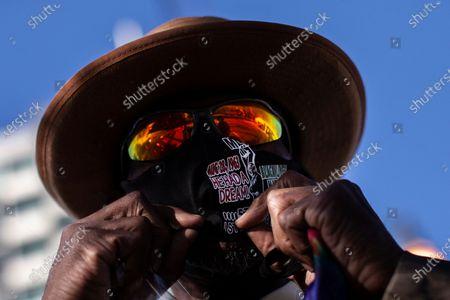 Anthony Wilson adjust his MLK mask on Dr. Martin Luther King Jr. Day, in Atlanta