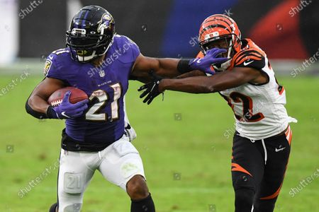 Shows Baltimore Ravens running back Mark Ingram (21) running the ball against Cincinnati Bengals cornerback William Jackson (22) during the second half of an NFL football game in Baltimore. The three-time Pro Bowl running back has been released by the Baltimore Ravens, who used the 10-year veteran as a starter for the first seven games this season before dropping him deep on the depth chart