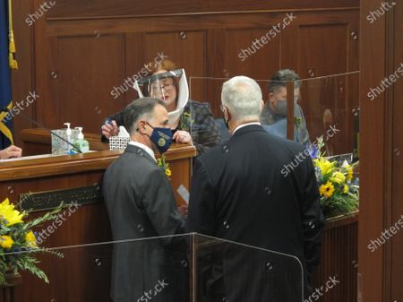 Stock Image of Alaska state Sens. Peter Micciche, left, and Gary Stevens, right, speak with Senate Secretary Liz Clark ahead of the Senate floor session, in Juneau, Alaska. Tuesday was the first day of the new legislative session