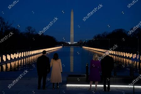 """With the Washington Monument in the background, President-elect Joe Biden with his wife Jill Biden and Vice President-elect Kamala Harris with her husband Doug Emhoff listen as Yolanda Adams sings """"Hallelujah"""" during a COVID-19 memorial, with lights placed around the Lincoln Memorial Reflecting Pool, in Washington"""