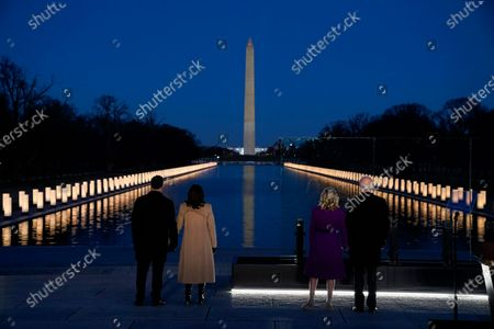 """Stock Image of With the Washington Monument in the background, President-elect Joe Biden with his wife Jill Biden and Vice President-elect Kamala Harris with her husband Doug Emhoff listen as Yolanda Adams sings """"Hallelujah"""" during a COVID-19 memorial, with lights placed around the Lincoln Memorial Reflecting Pool, in Washington"""