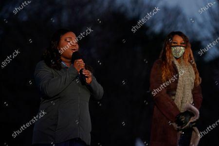 "Yolanda Adams, right, listens as Michigan nurse Lori Marie Key sings ""Amazing Grace"" during a COVID-19 memorial, in Washington"