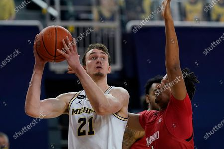 Michigan guard Franz Wagner (21) looks towards the basket at Maryland forward James Graham III (1) defends during the second half of an NCAA college basketball game, in Ann Arbor, Mich