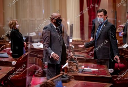 Senators Steven Bradford (D-Gardena), left, and Brian Jones (D-Santee) speak through face masks and plexiglass partitions set up in the Senate chamber because of Covid during a session in the Capitol on January 19, 2021 in Sacramento, California. This is the first time the Senate has met since the Insurrection at the U.S. Capitol on January 6. (Gina Ferazzi / Los Angeles Times)