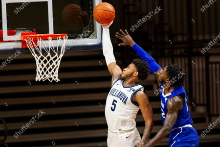 Villanova guard Justin Moore (5) is followed to the basket bay Seton Hall guard Myles Cale (22) during the first half of an NCAA college basketball game, in Villanova, Pa