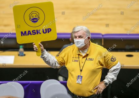 An usher holds a sign telling fans to ''mask up'' during NCAA Basketball action between the Alabama Crimson Tide and the LSU Tigers at the Pete Maravich Assembly Center in Baton Rouge, LA