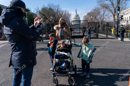 Gavin Coleman, owner of The Dubliner Restaurant, takes a photograph of his wife, Alexandra Coleman, and their sons, Henry, 6, Taylor, 4, and Peter, 2, by the anti-scaling fence protecting the U.S. Capitol compound, in Washington, as security is increased ahead of the inauguration of President-elect Joe Biden and Vice President-elect Kamala Harris. The Colemans live in the Capitol Hill neighborhood around the corner from the Capitol and are re-opening their restaurant to accommodate diners staying in the hotel above their restaurant for inauguration