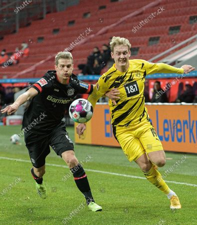 Julian Brandt (R) of Dortmund vies with Lars Bender of Leverkusen during a German Bundesliga football match between Bayer 04 Leverkusen and Borussia Dortmund in Leverkusen, Germany, Jan. 19, 2021.