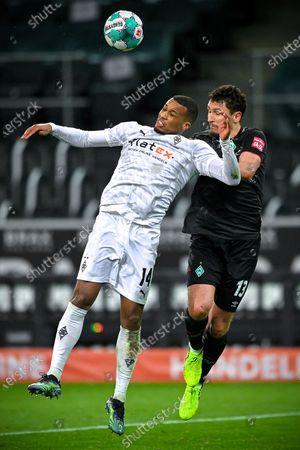 Alassane Plea (L) of Moenchengladbach vies for a header with Milos Veljkovic of Bremen during a German Bundesliga football match between Borussia Moenchengladbach and SV Werder Bremen in Moenchengladbach, Germany, Jan. 19, 2021.