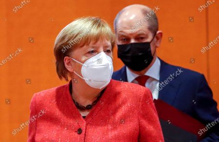 German Chancellor Angela Merkel and Finance Minister Olaf Scholz wear protective masks as they attend the weekly cabinet meeting at the Chancellery in Berlin, Germany