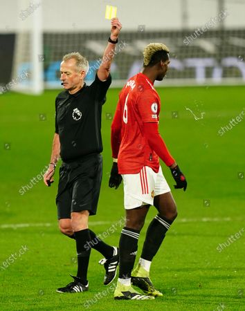Paul Pogba of Manchester United spits as he is booked by referee Martin Atkinson