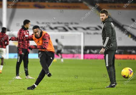 Anthony Martial of Manchester United warming up as coach Michael Carrick looks on