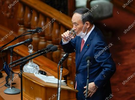 Japanese Prime Minister Yoshihide Suga drinks water before answering opposition Constitutional Democratic Party of Japan leader Yukio Edano during a parliamentary session for answering questions to his policy speech in Tokyo, Japan, 20 January 2021. The government policies for new coronavirus pandemic and Tokyo 2020 Olympic Games are the focus for the ordinary Diet session.