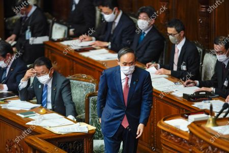 Japanese Prime Minister Yoshihide Suga (C) walks toward podium to answer Opposition Constitutional Democratic Party of Japan leader Yukio Edano during a parliamentary session for answering questions to his policy speech in Tokyo, Japan, 20 January 2021. The government policies for new coronavirus pandemic and Tokyo 2020 Olympic Games are the focus for the ordinary Diet session.