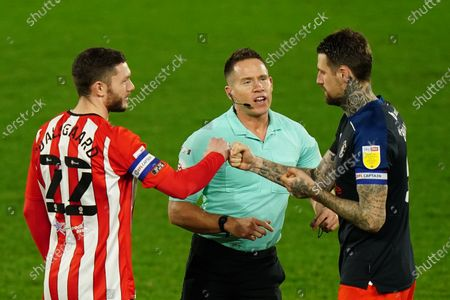 Henrik Dalsgaard of Brentford bumps fists with Sonny Bradley of Luton Town as they join Referee Steve Martin for the coin toss
