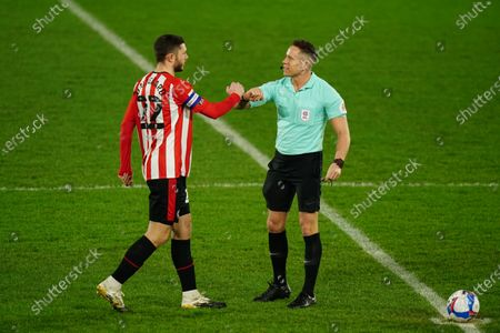 Stock Photo of Henrik Dalsgaard of Brentford bumps fists with Referee Steve Martin