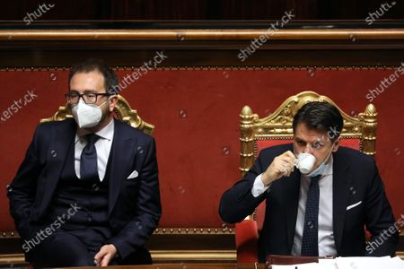 Giuseppe Conte, Italy's prime minister, right, drinks a coffee speaks flanked by Alfonso Bonafede, Italy's justice minister, during a debate in the Senate in Rome. Prime Minister Giuseppe Conte waged a charm offensive Tuesday in the Italian Senate ahead of a vote that will decide whether his coalition can survive