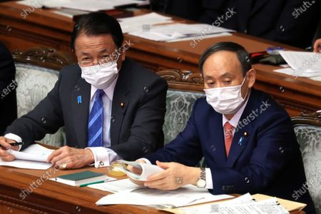Japanese Prime Minister Yoshihide Suga (R) and Finance Minister Taro Aso listen to a question at Lower House's plenary session at the National Diet in Tokyo on Wednesday, January 20, 2021. Ruling and opposition parties questioned to Suga as Suga delivered his policy speech at the beginning of an ordinary Diet session on January 18.