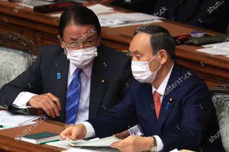 Japanese Prime Minister Yoshihide Suga (R) chats with Finance Minister Taro Aso (L) at Lower House's plenary session at the National Diet in Tokyo on Wednesday, January 20, 2021. Ruling and opposition parties questioned to Suga as Suga delivered his policy speech at the beginning of an ordinary Diet session on January 18.