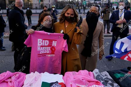 Chrissy Teigen, center, and her mother Vilailuck Teigen shop for President Joe Biden and Vice President Kamala Harris and John Legend for souvenirs during 59th Presidential Inauguration, in Washington