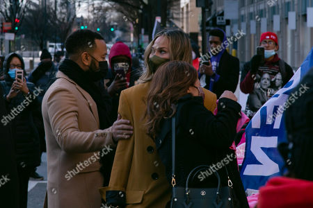 John Legend, Chrissy Teigen and her mother, Vilailuck Teigen, purchase Biden/Harris memorabilia at Black Lives Matter Plaza near the White House on Inauguration Day