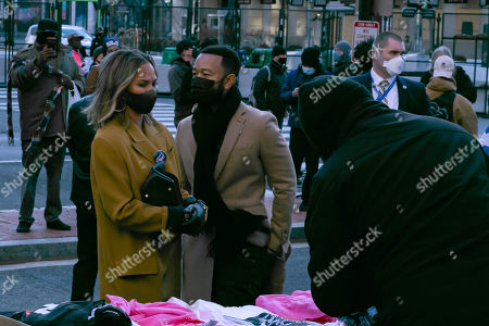 John Legend and Chrissy Teigen purchase Biden/Harris memorabilia at Black Lives Matter Plaza near the White House on Inauguration Day