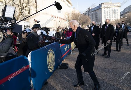 Stock Photo of President Joe Biden talks with Washington, NBC anchor Al Roker, as he and and First Lady Jill Biden walk along Pennsylvania Avenue in front of the White House during Inaugural celebrations, Wednesday, Jan. 20, 202, after being sworn in as the 46th vice president of the United States