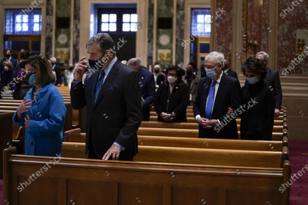 House Speaker Nancy Pelosi, left, and her husband Paul Pelosi and Senate Minority Leader Mitch McConnell and his wife Elaine Chao attend Mass at the Cathedral of St. Matthew the Apostle during Inauguration Day ceremonies, in Washington