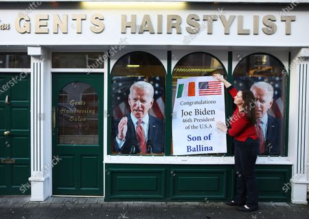 Catherine Hallahan puts a poster up on the family business congratulating Joe Biden becoming the 46th president of the U.S., in Ballina, Ireland, . The town, situated on the west coast of Ireland, is the ancestral home of Joe Biden