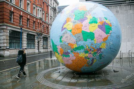 """Stock Photo of A pedestrian walks past the globe sculpture designed by by Mark Wallinger """"The World Turned Upside Down"""" outside the London  School of Economics. The UK has recorded a new  new daily high on Tuesday from covid-19 related deaths and the higest  in a single day since the coronavirus pandemic began."""