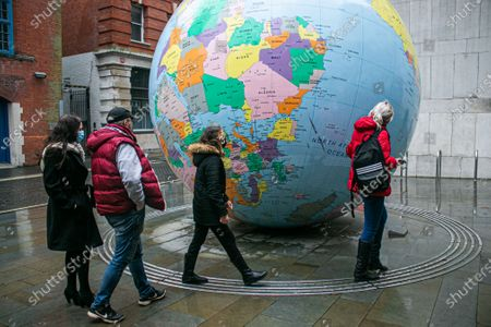 """Pedestrians walks past the globe sculpture designed by by Mark Wallinger """"The World Turned Upside Down"""" outside the London  School of Economics. The UK has recorded a new  new daily high on Tuesday from covid-19 related deaths and the higest  in a single day since the coronavirus pandemic began."""