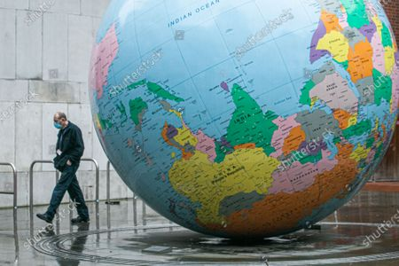 """A pedestrian walks past the globe sculpture designed by by Mark Wallinger """"The World Turned Upside Down"""" outside the London  School of Economics. The UK has recorded a new  new daily high on Tuesday from covid-19 related deaths and the higest  in a single day since the coronavirus pandemic began."""