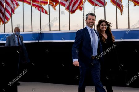 Donald Trump Jr., executive vice president of development and acquisitions for Trump Organization Inc., left, and his partner Kimberly Guilfoyle, arrive to a farewell ceremony at Joint Base Andrews, Maryland, U.S.,. Trump departs Washington with Americans more politically divided and more likely to be out of work than when he arrived, while awaiting trial for his second impeachment - an ignominious end to one of the most turbulent presidencies in American history.